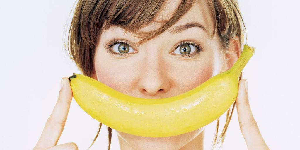 Девушка держит банан перед ртом