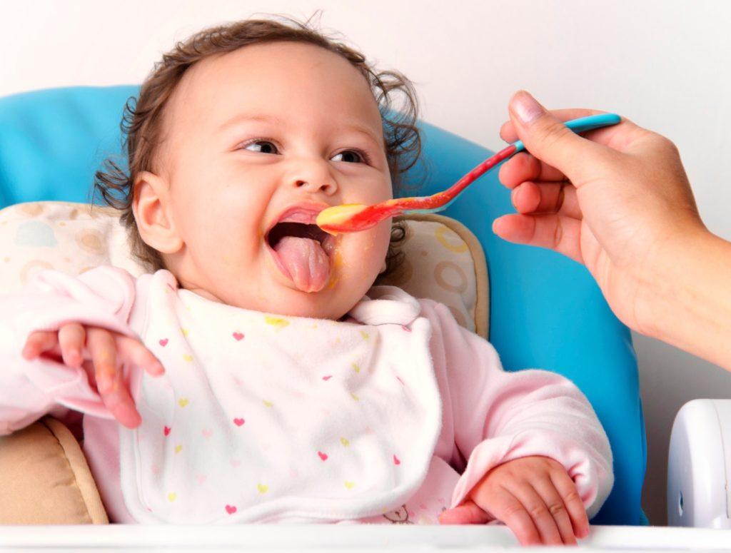 Ребенок открывает рот перед ложкой с пюре