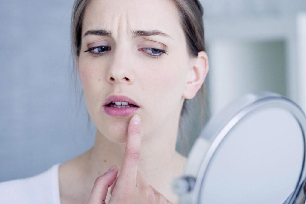 Женщина касается губы и смотрит в зеркало
