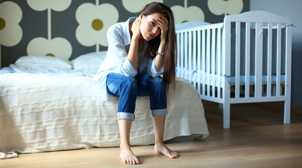 Уставшая молодая женщина сидит возле детской кроватки
