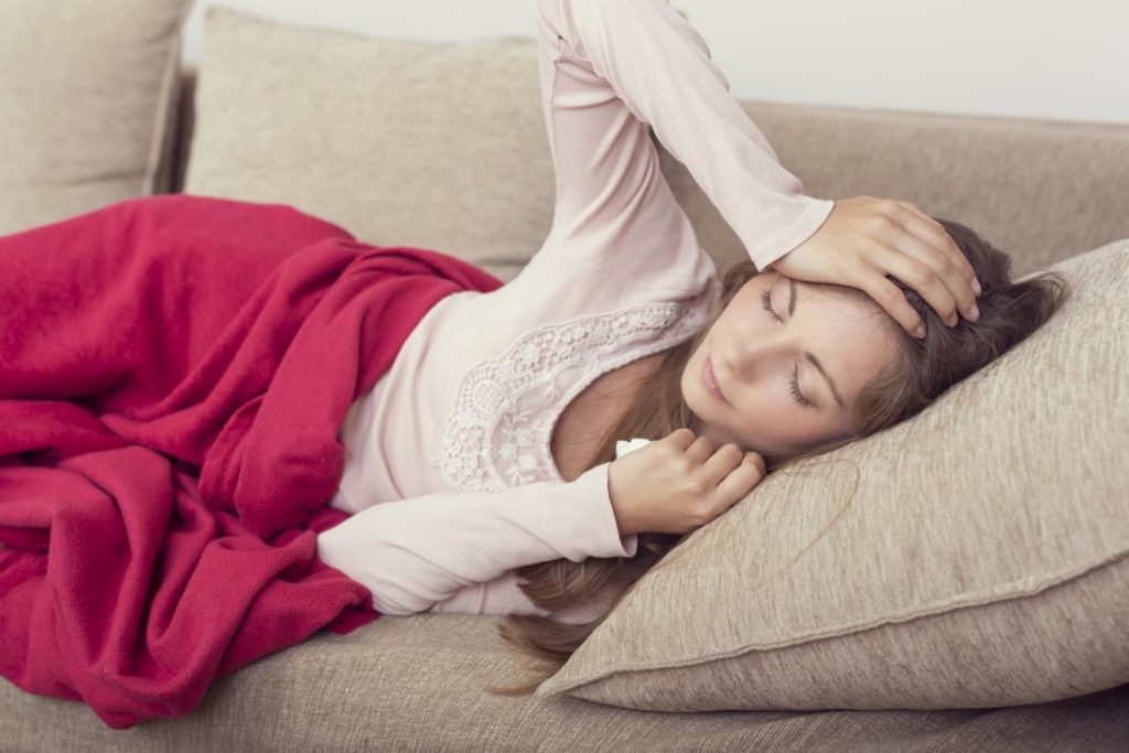 Женщина лежит на диване и держится за голову