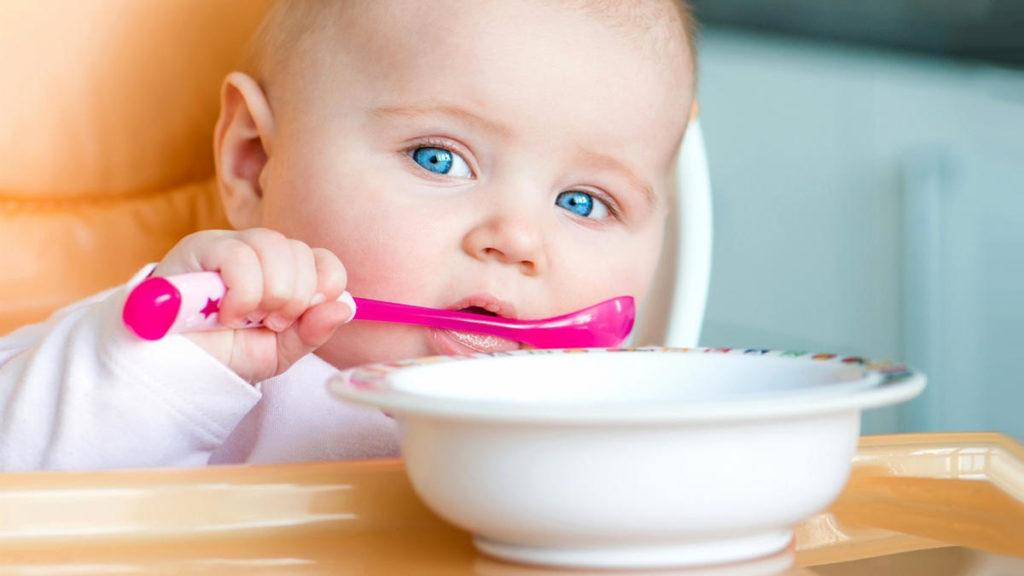 Ребенок держит ложку, на столе стоит тарелка