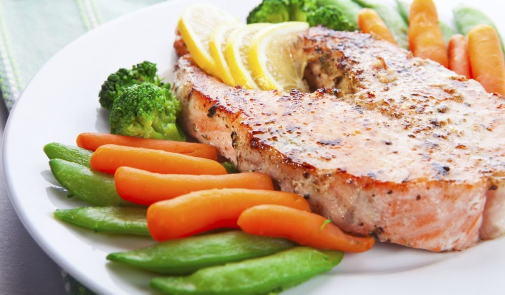 Стейк рыбы с овощами на тарелке
