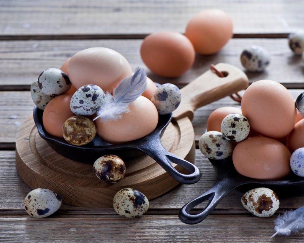 Перепелиные и куриные яйца на сковородке на столе