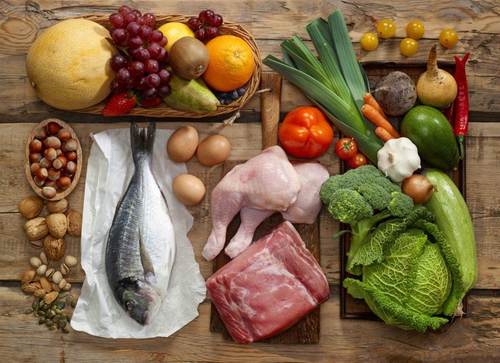 Мясо, рыба, овощи, фрукты лежат на столе