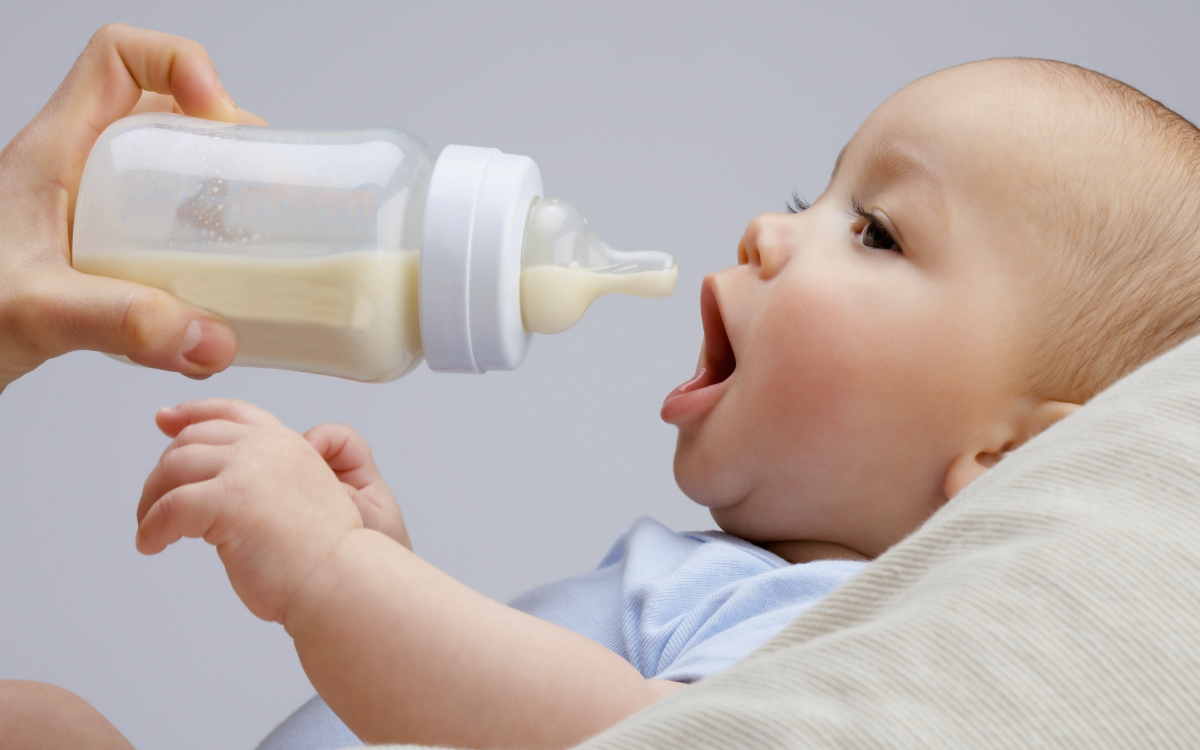 Ребенку дают бутылочку со смесью