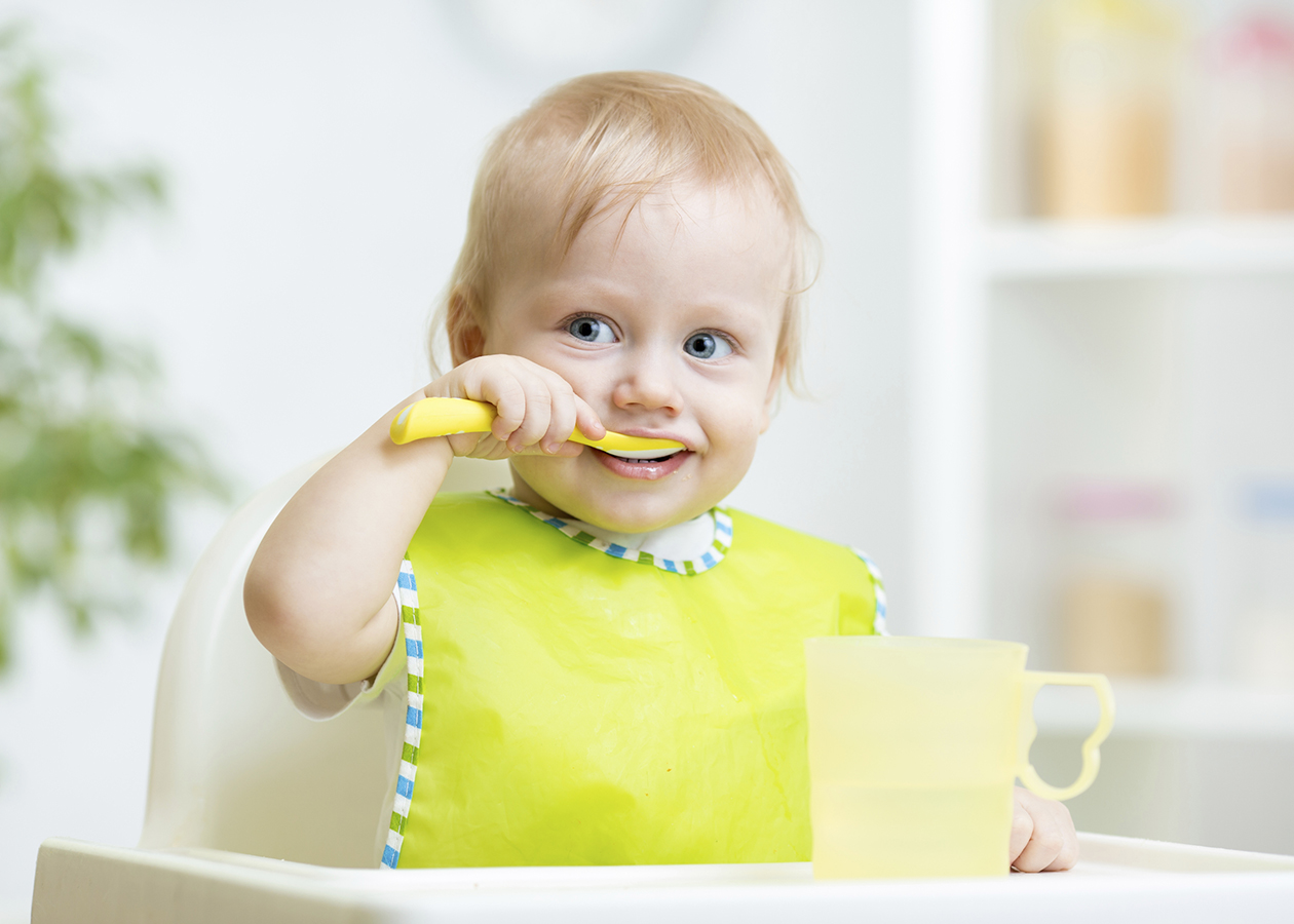 Ребенок сидит за столом и ест ложкой