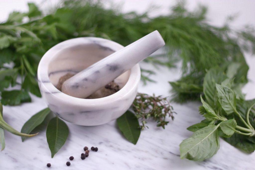 Ступка, пестик и травы на столе