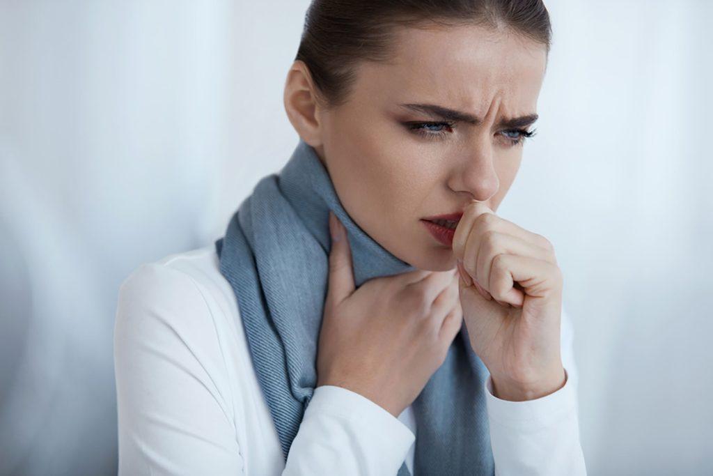 Женщина кашляет и держится рукой за горло