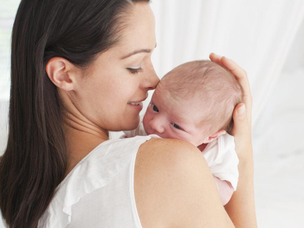 Улыбающаяся мама держит ребенка на руках