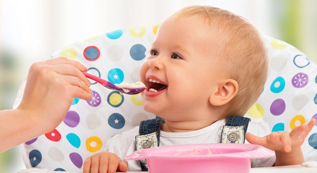 Ребенок улыбается и ему дают ложку с едой