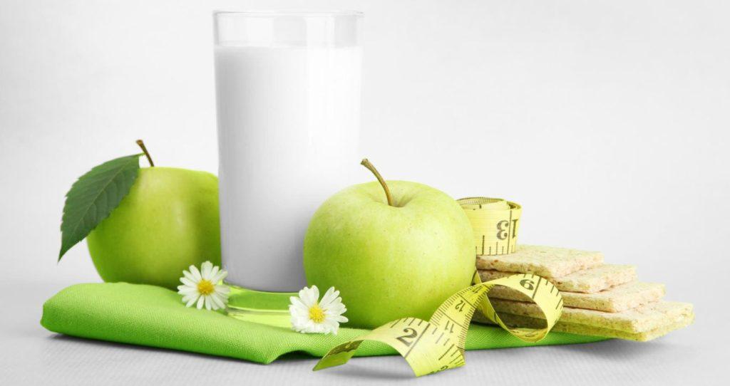 Стакан кефира, два яблока и сантиметровая лента на зеленой салфетке на белом фоне