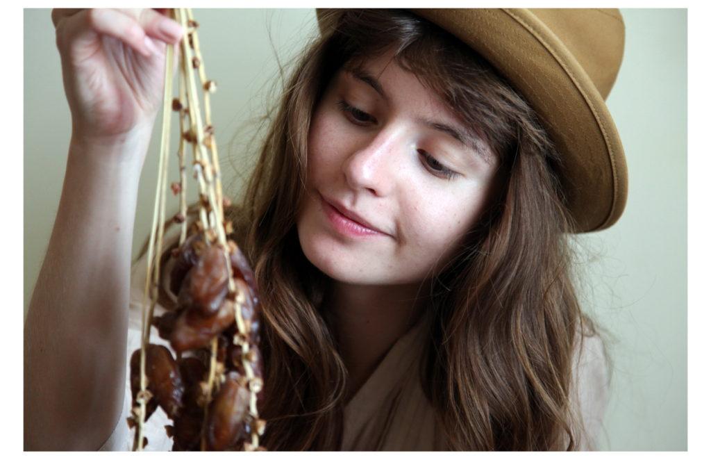 Девушка смотрит на связку фиников