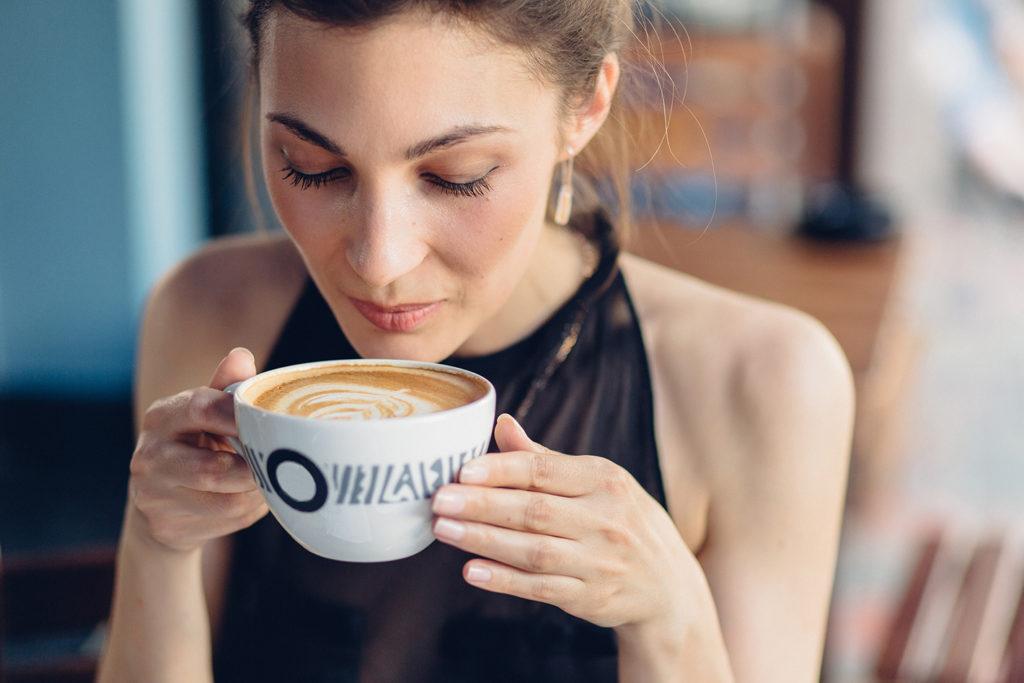 Девушка пьет кофе из чашки в кафе