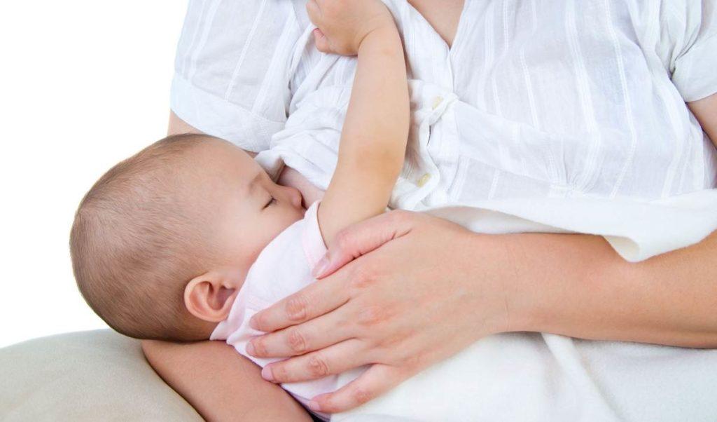 Ребенок сосет грудь на руках у мамы
