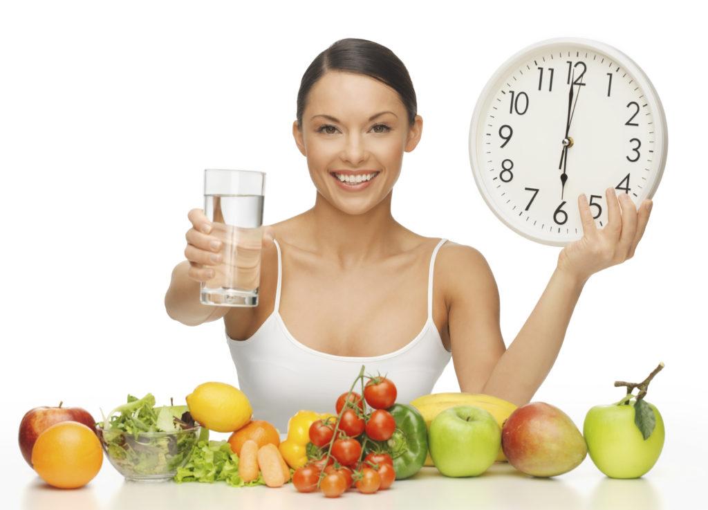 Девушка сидит за столом с овощами и фруктами и держит в руках стакан воды и часы