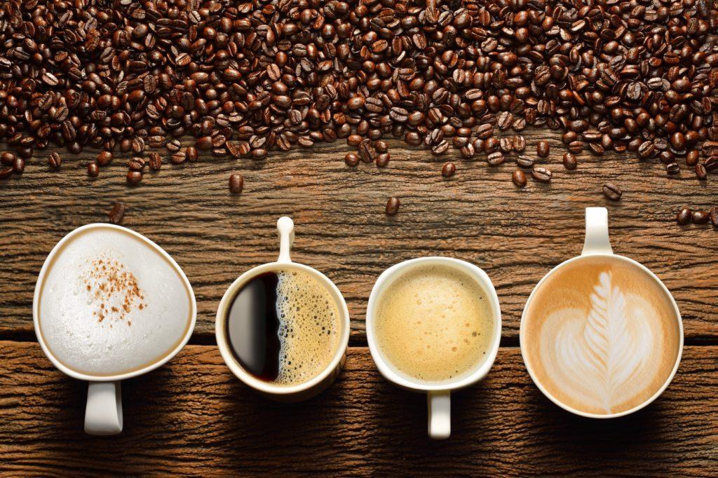 Четыре чашки с разными видами кофе и кофейные зерна на столе