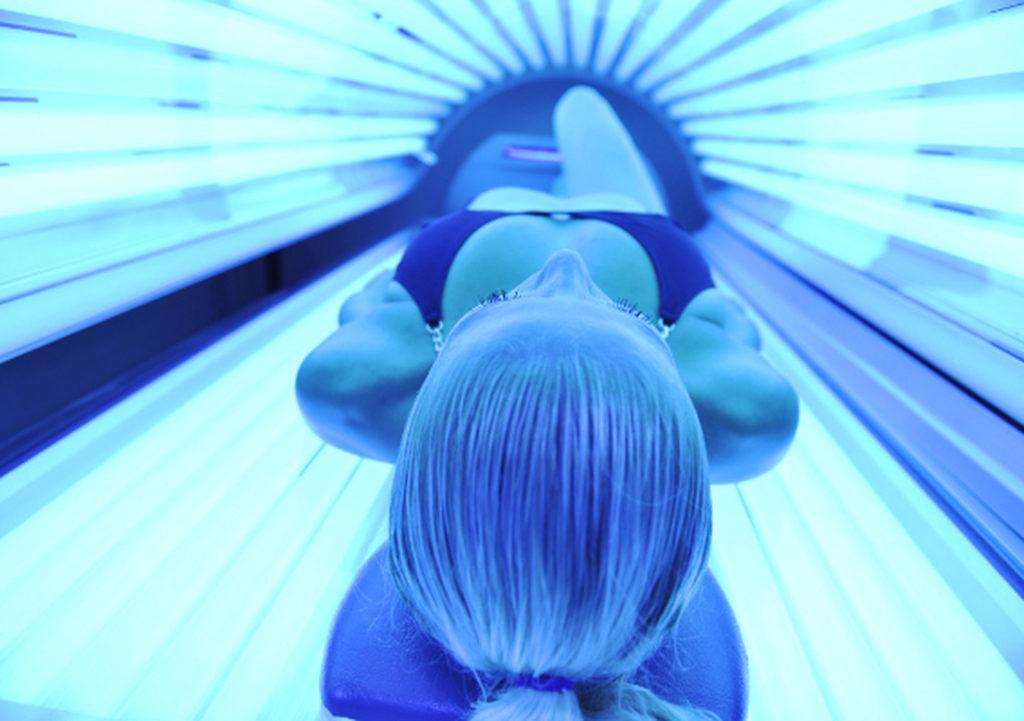 Девушка в купальнике загорает лежа в солярии