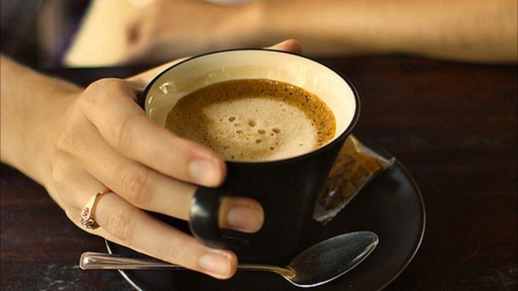 Женская рука держит чашку кофе
