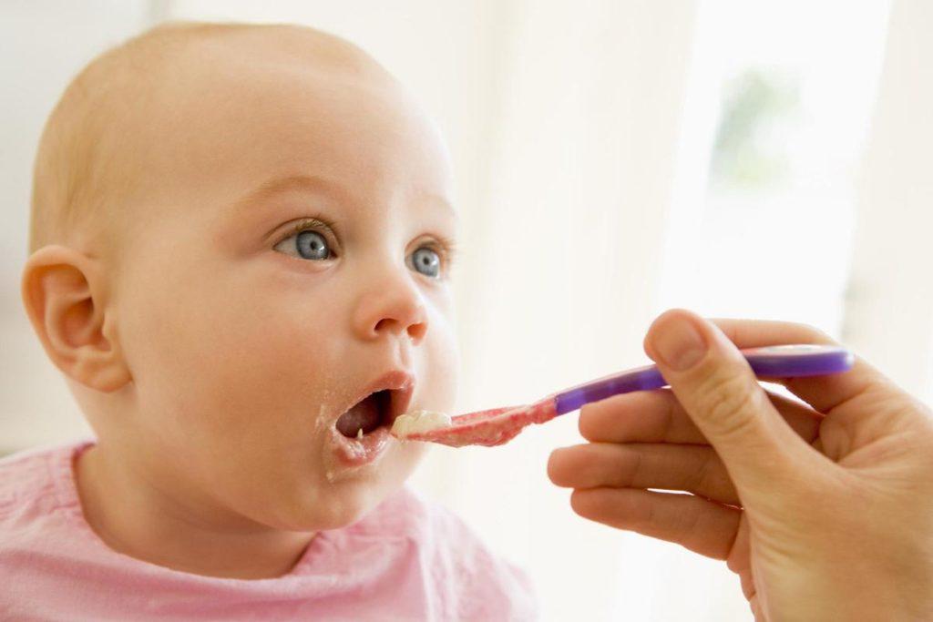 Ребенок открыл рот, ему дают прикорм с ложки
