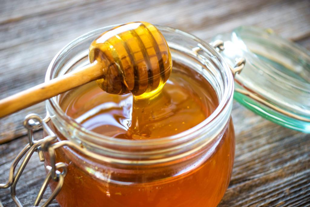 Мед в открытой стеклянной банке на деревянном столе
