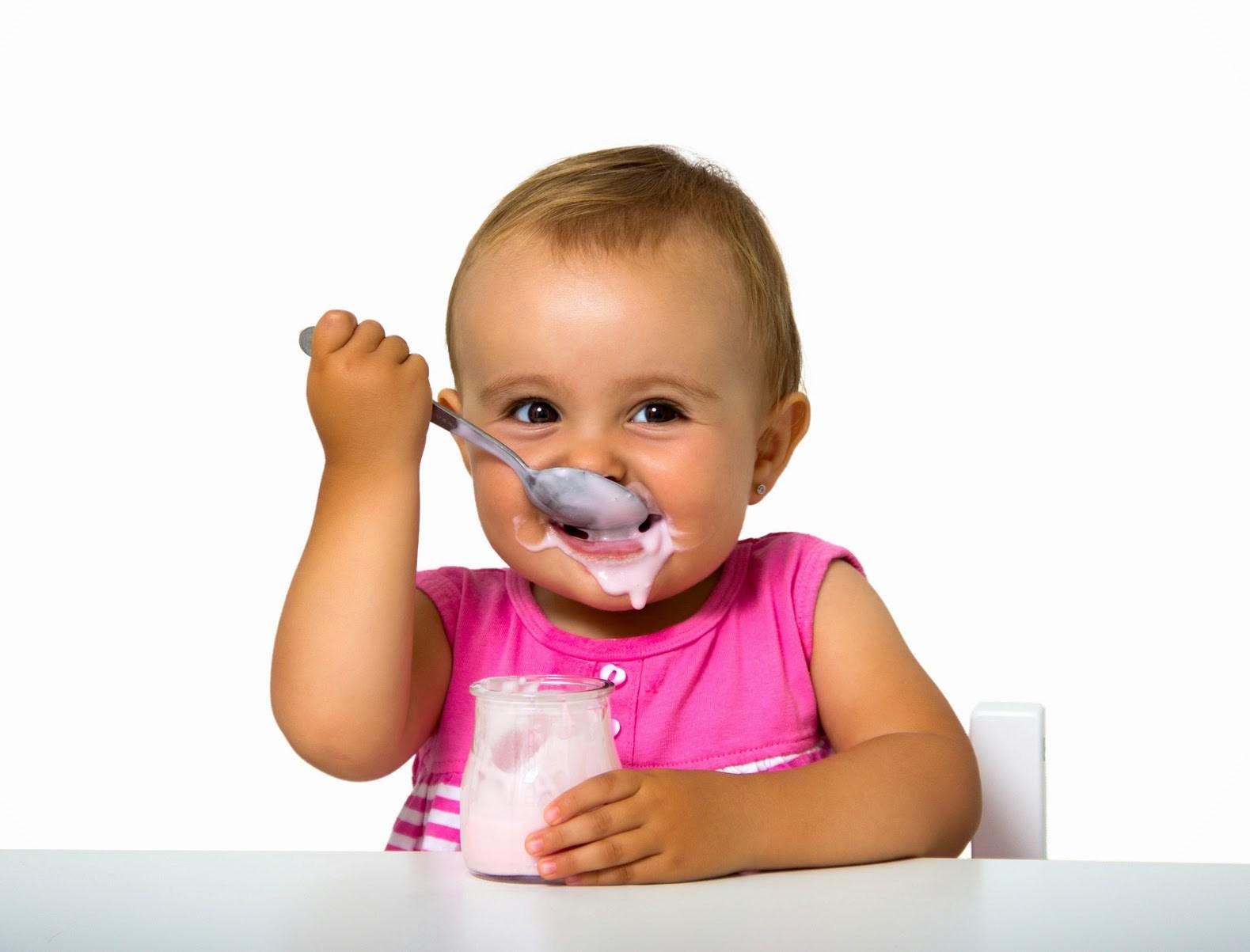 ребенок ест ложкой йогурт из банки