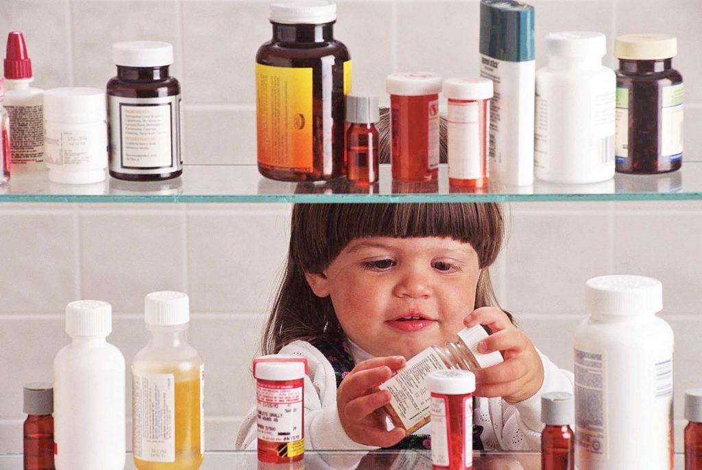 Ребенок берет банки с лекарствами с полки