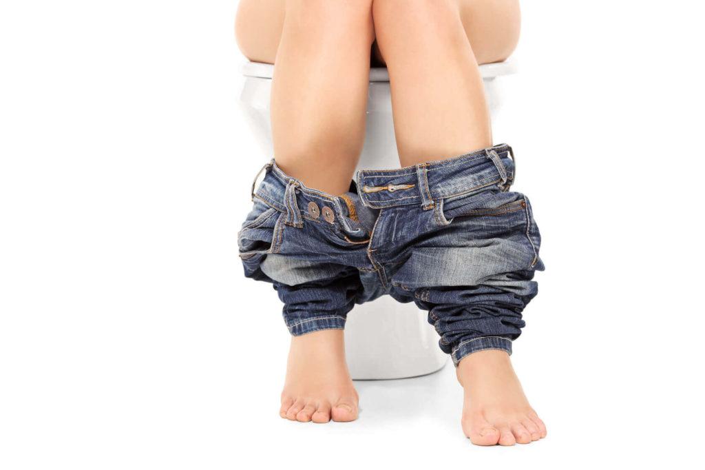 Девушка сидит на унитазе со спущенными джинсами