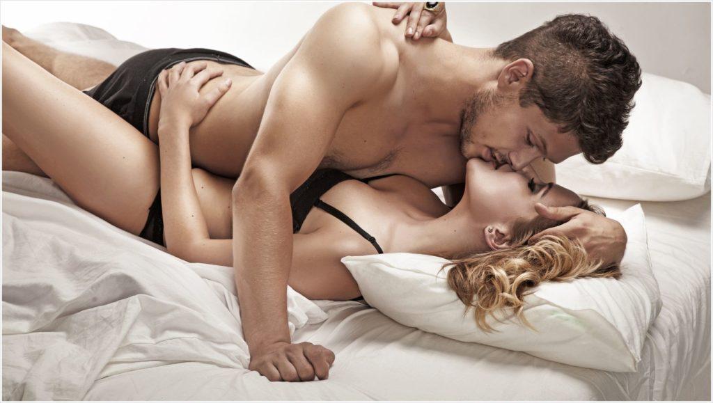 Мужчина и женщина занимаются сексом лежа в кровати