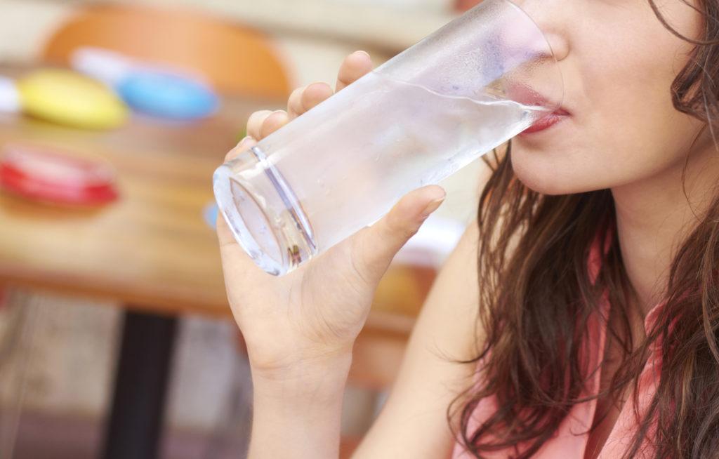 Девушка пьет воду из стеклянного стакана