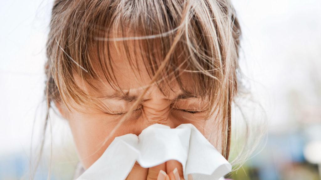 Девушка высмаркивает нос в платок