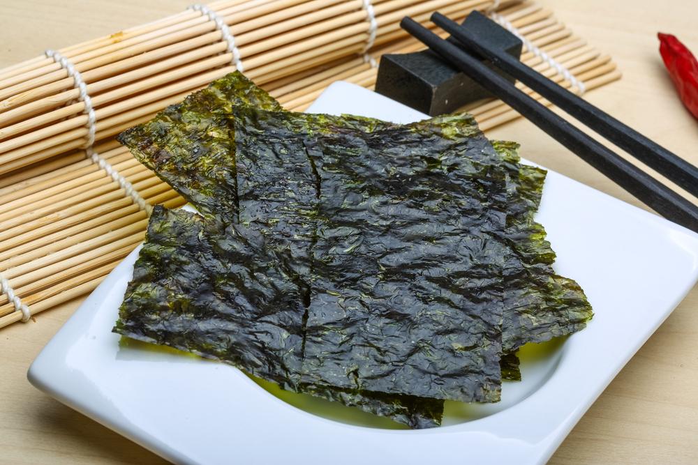 Нори на белой тарелке на фоне бамбукового коврика для суши и палочек