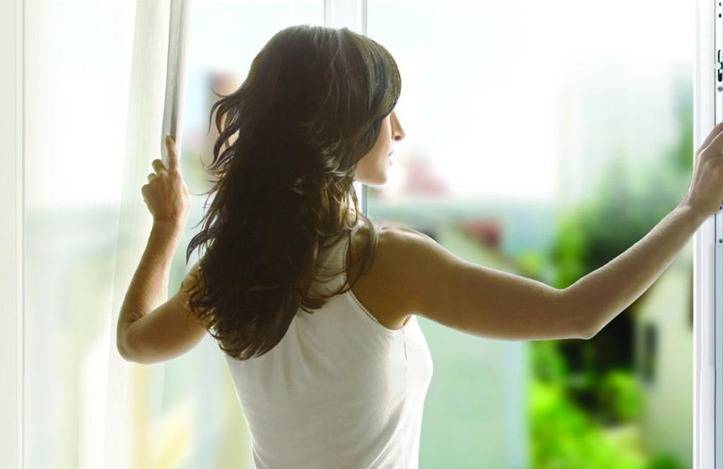 Девушка стоит лицом к открытому окну
