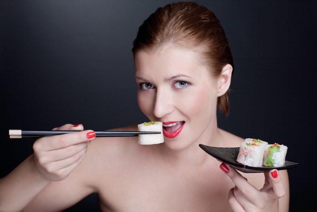 Красивая девушка ест суши на черном фоне