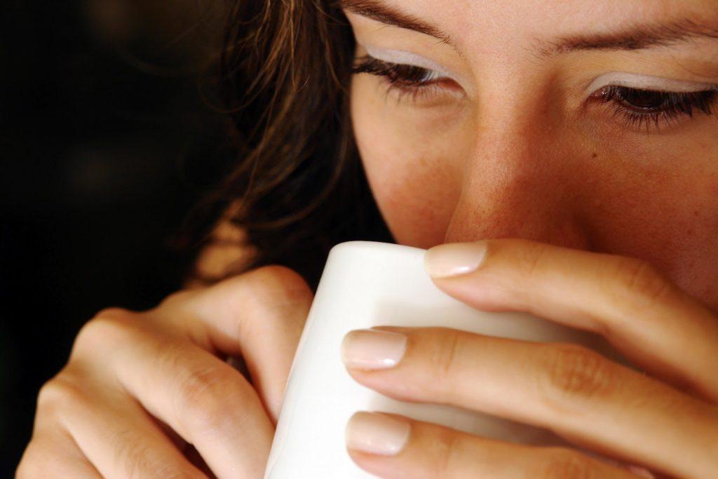 Девушка пьет из белой кружки