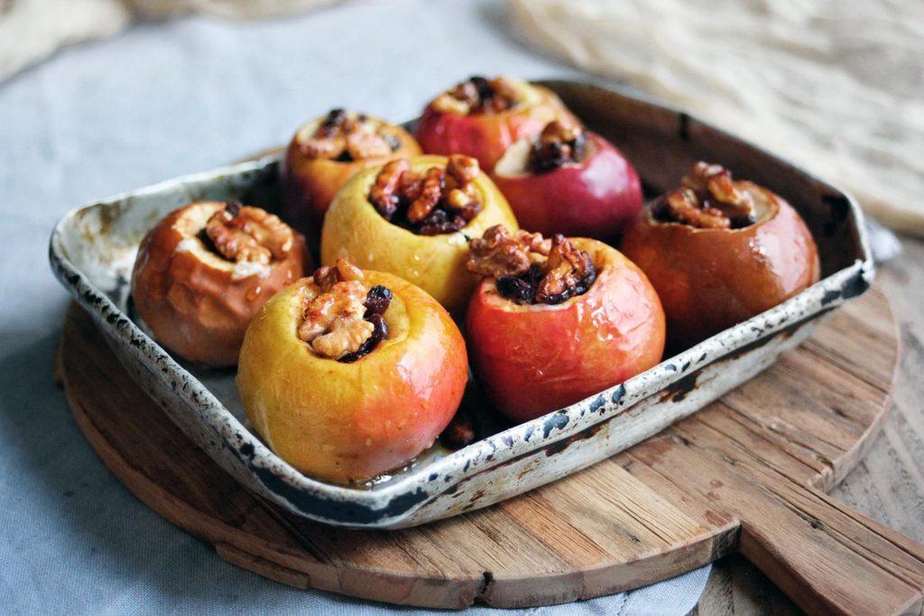 Печеные яблоки с изюмом и орехами в противне на столе