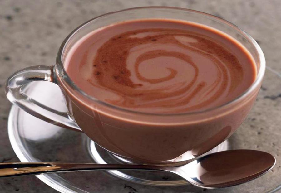 Какао в прозрачной чашке на блюдце с ложкой