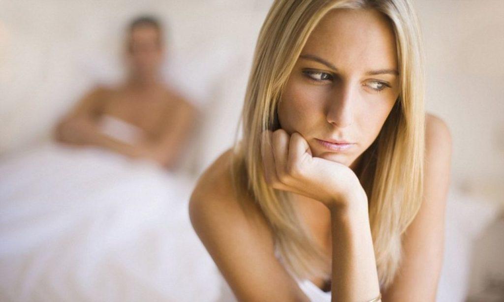 Задумчивая девушка на фоне мужчины в постели