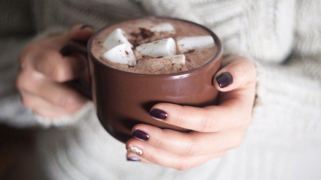 Какао с маршмеллоу в коричневой кружке в руках у девушки