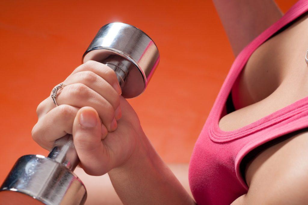 Женская грудь и гантеля в руке перед грудью