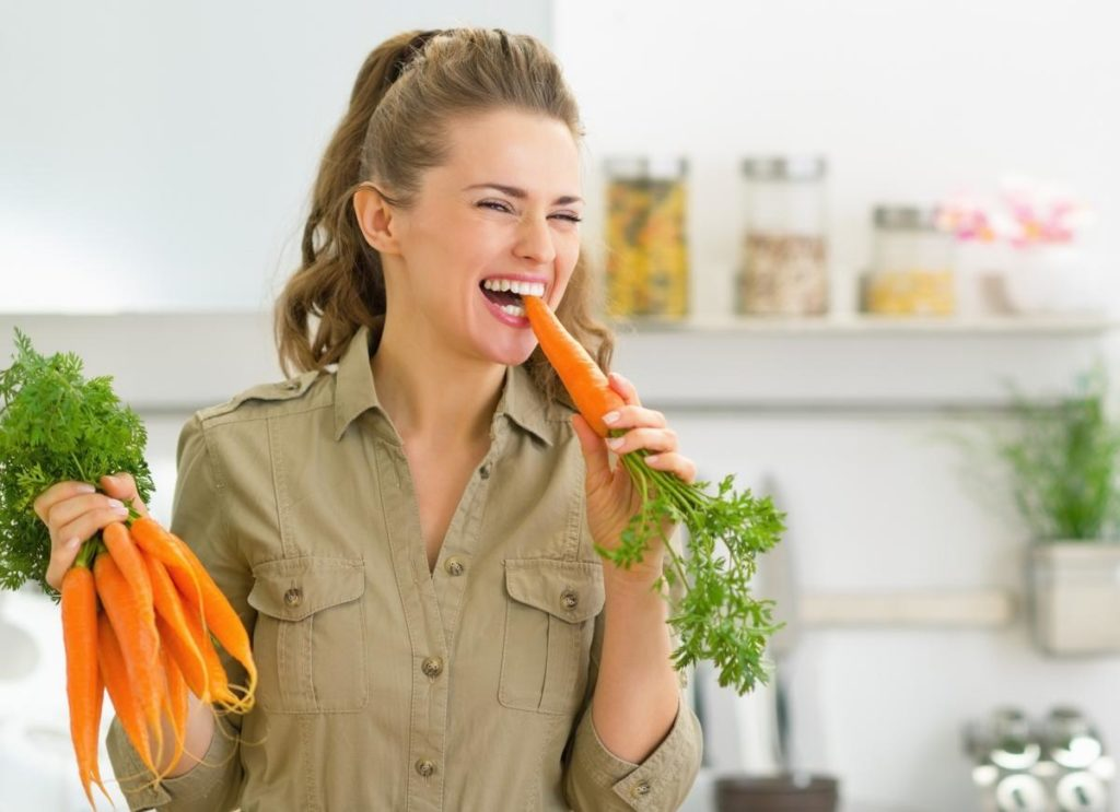 Девушка ест морковь на кухнке и держит в руке связку моркови