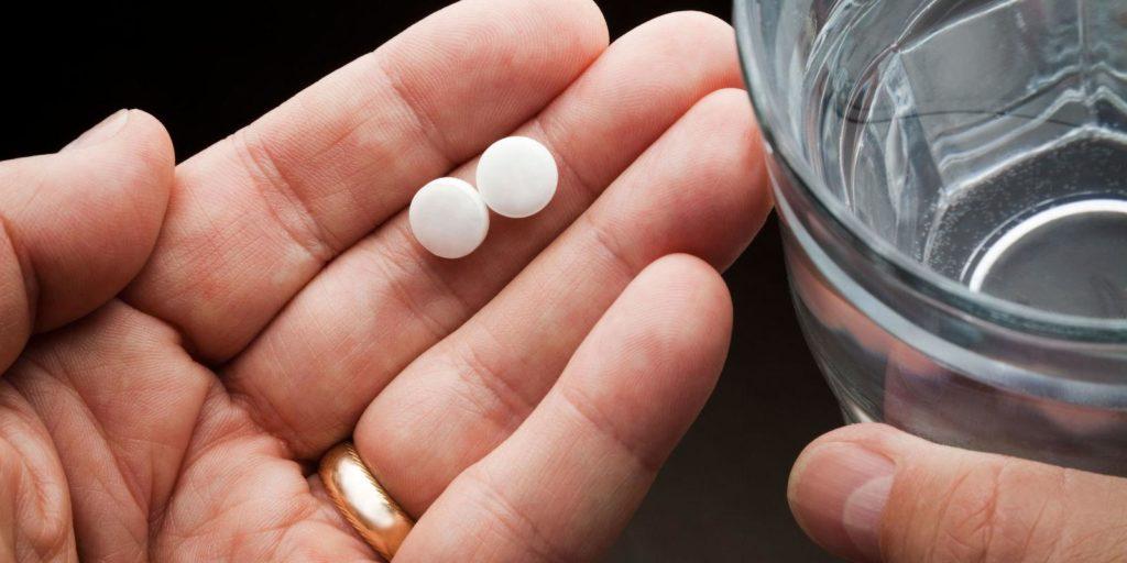 Две белые таблетки на ладони и стакан воды