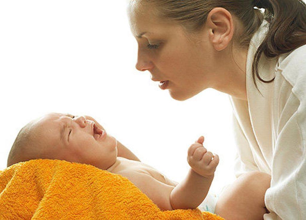 Мама склонилась над плачущим младенцем