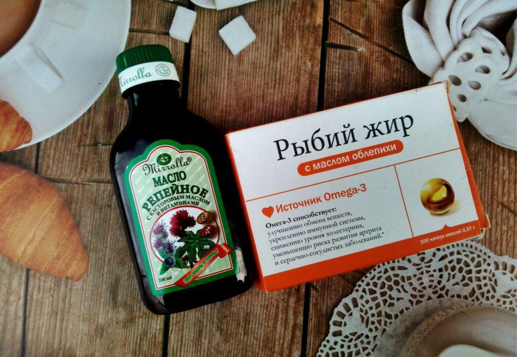 Репейное масло и рыбий жир на деревянном столе