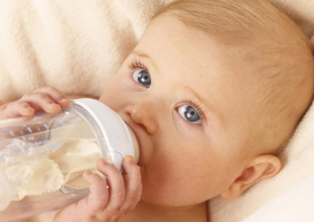 Ребенок сосет бутылочку