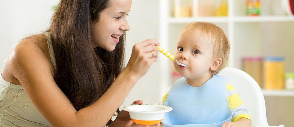 Молодая мама кормит ребенка с ложечки