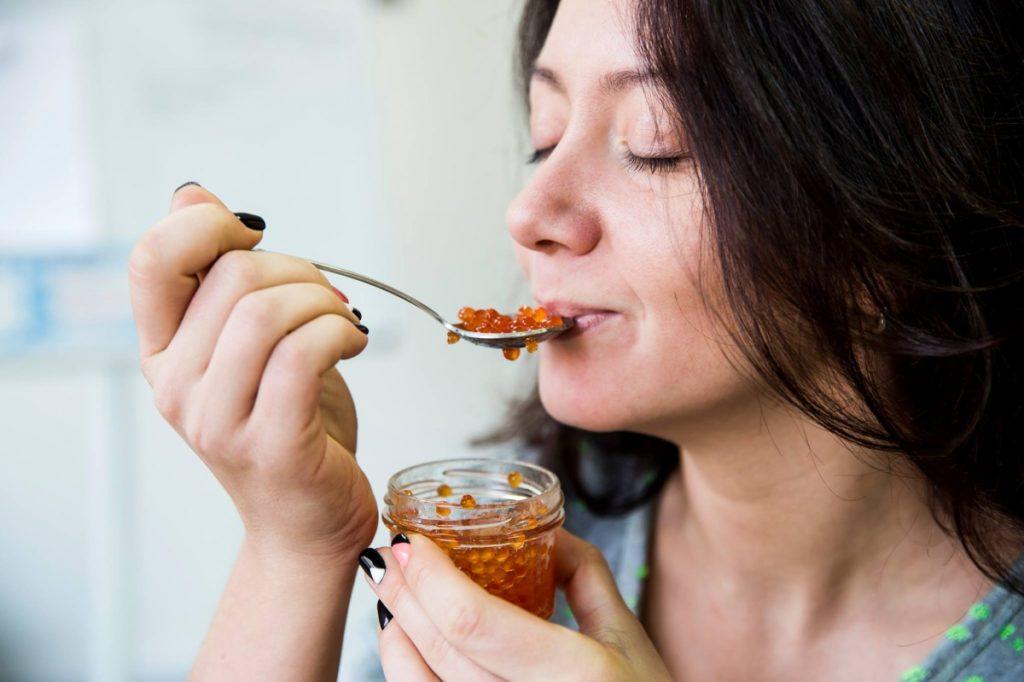 Девушка ест красную икру ложкой из банки