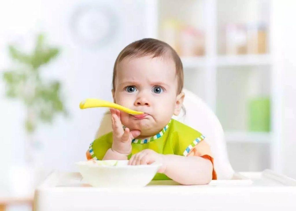 Нахмуренный ребенок сидит в детсско стульчике и держит ложку во рту