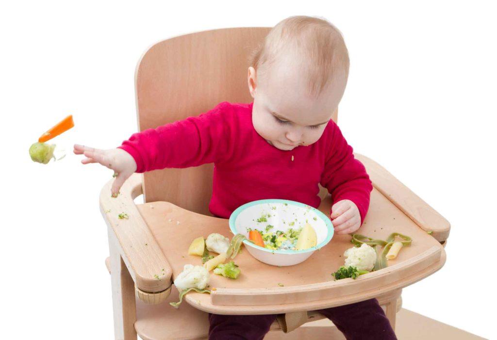 Ребенок сидит в детском стуле и разбрасывает вареные овощи