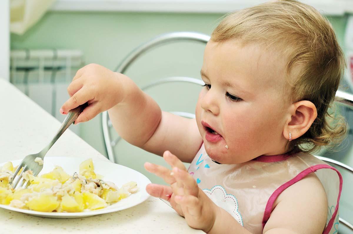 Маленькая девочка за столом ест сама вилкой